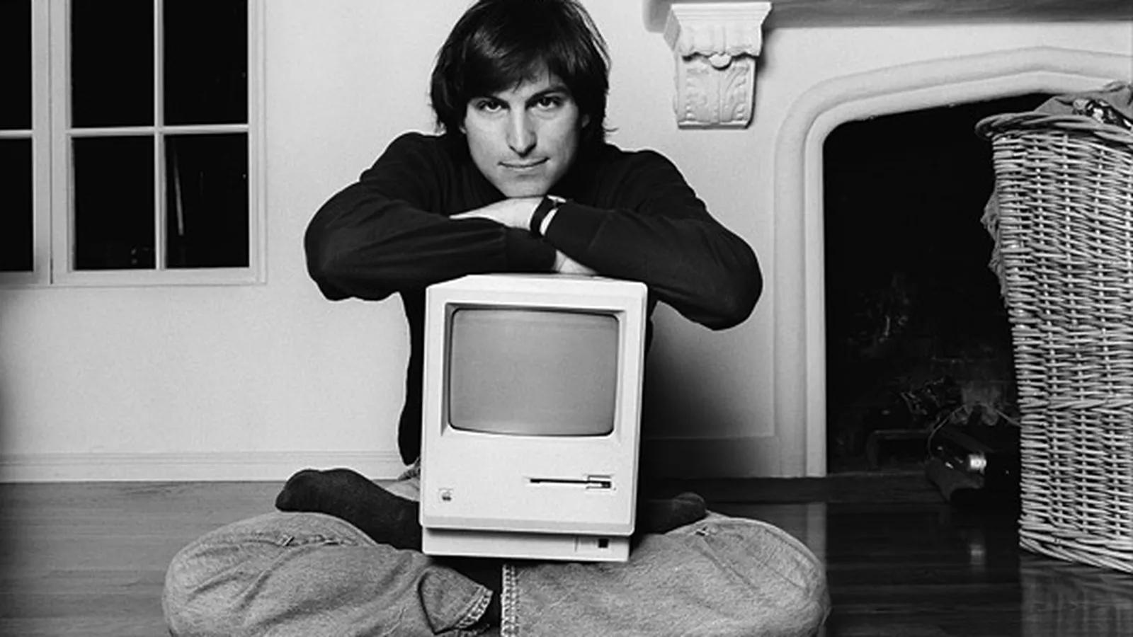 Steve Jobs sentado com o primeiro Macintosh nas pernas